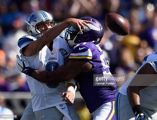 Matthew Stafford of the Detroit Lions attempts to pass the ball under pressure by Everson Griffen of the Minnesota Vikings during the fourth quarter...