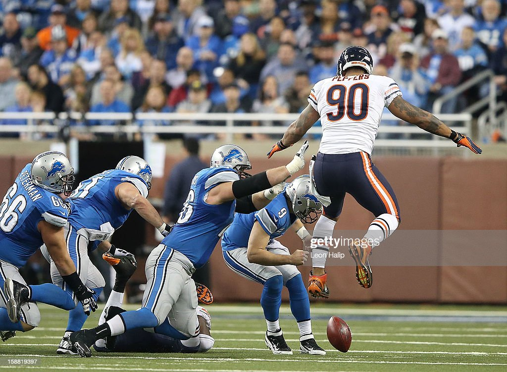 Matthew Stafford #9 of the Detroit Lions attempts to pick up the fumbled ball as Julius Peppers #90 of the Chicago Bears gives chase during the third quarter of the game at Ford Field on December 30, 2012 in Detroit, Michigan. The Bears defeted the Lions 26-24.