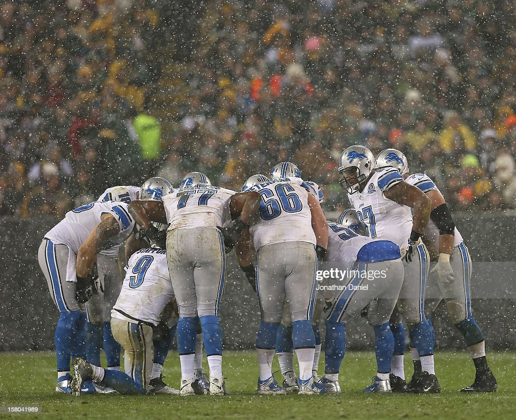 Matthew Stafford #9 of the Detroit Lions calls a play in the huddle as it snows during a game against Green Bay Packers at Lambeau Field on December 9, 2012 in Green Bay, Wisconsin.
