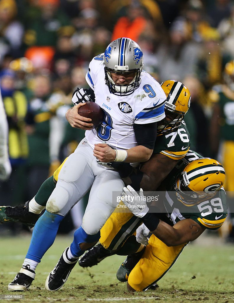 Matthew Stafford #9 of the Detroit Lions carries the ball for a first down as he is tackled by Mike Daniels #76 and Brad Jones #59 of the Green Bay Packers in the fourth quarter at Lambeau Field on December 28, 2014 in Green Bay, Wisconsin.