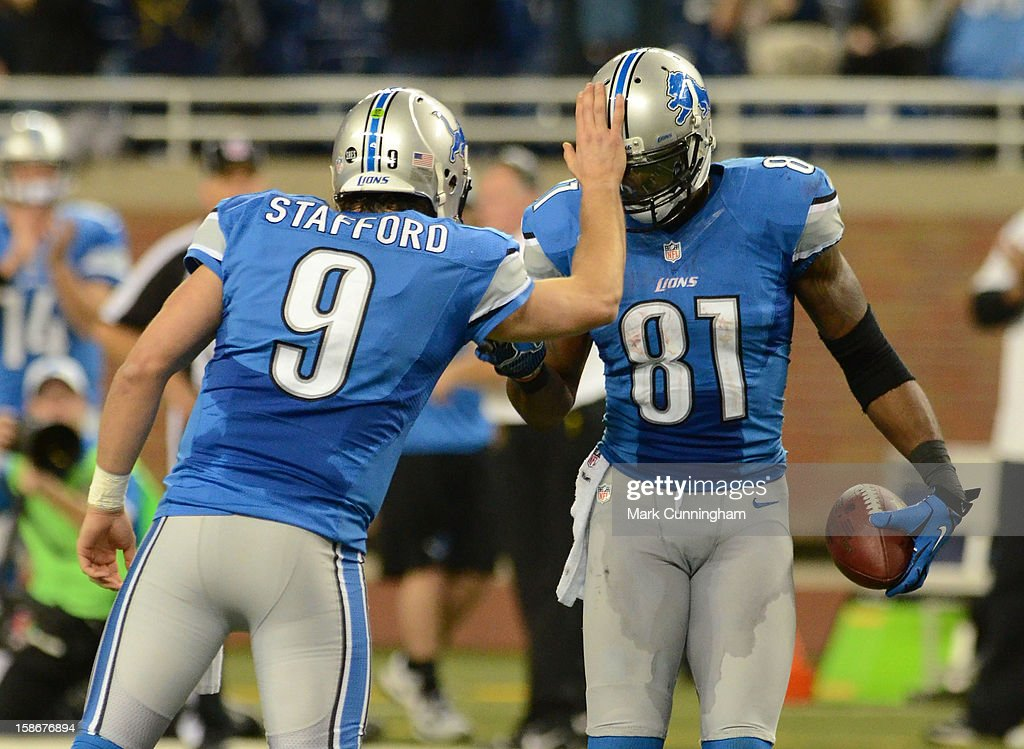 Matthew Stafford #9 of the Detroit Lions congratulates Calvin Johnson #81 after Johnson broke the NFL single season yardage record formally held by Jerry Rice with a 26-yard catch in the fourth quarter of the game against the Atlanta Falcons at Ford Field on December 22, 2012 in Detroit, Michigan. The Falcons defeated the Lions 31-18.