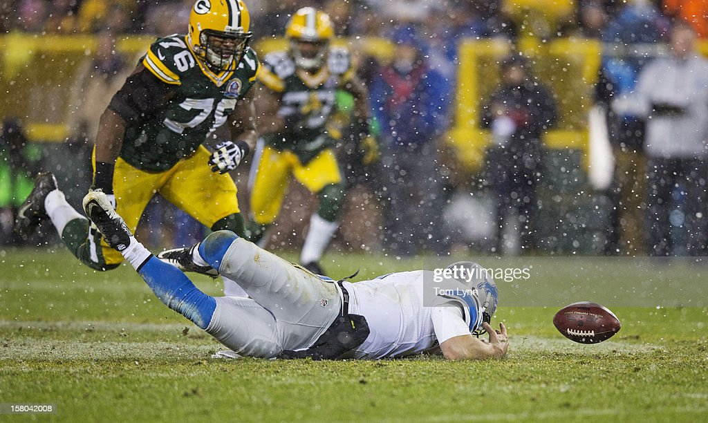 Matthew Stafford #9 of the Detroit Lions dives for the ball he fumbled as Mike Daniels #76 of the Green Bay Packers closes in at Lambeau Field on December 9, 2012 in Green Bay, Wisconsin.