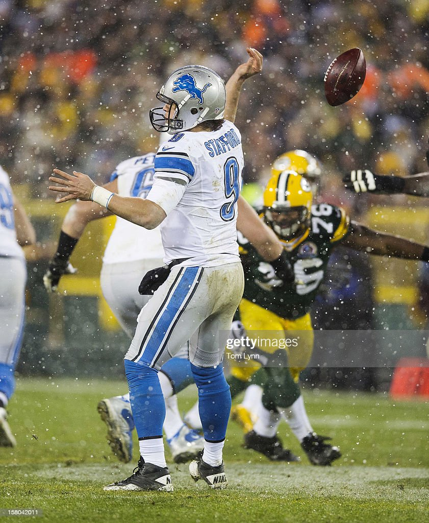 Matthew Stafford #9 of the Detroit Lions has the ball slip out of his hand as he tries to make a pass against the Green Bay Packers at Lambeau Field on December 9, 2012 in Green Bay, Wisconsin.