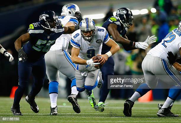 Matthew Stafford of the Detroit Lions is tackled by Cliff Avril of the Seattle Seahawks during the second half of the NFC Wild Card game at...