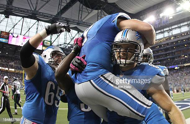 Matthew Stafford of the Detroit Lions runs one yard for a fourth quarter touchdown and is congratulated by teammates Dylan Gandy and Will Heller...