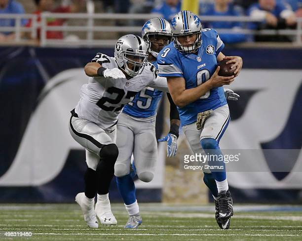 Matthew Stafford of the Detroit Lions tries to avoid being tackled by Taylor Mays of the Oakland Raiders in the second half at Ford Field on November...