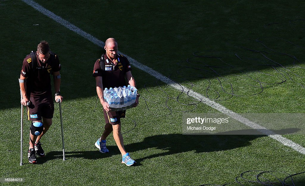 Matthew Suckling of the Hawthorn Hawks walks to the bus on crutches with fitness coach Andrew Russell after sustaining a right leg injury during the round three NAB Cup AFL match between the Hawthorn Hawks and the Richmond Tigers at Aurora Stadium on March 9, 2013 in Launceston, Australia.
