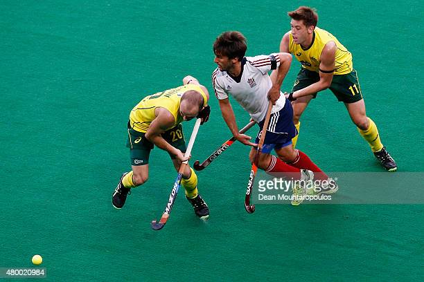 Matthew Swann and Eddie Ockenden of Australia battle for the ball with Adam Dixon of Great Britain during the Fintro Hockey World League SemiFinal...
