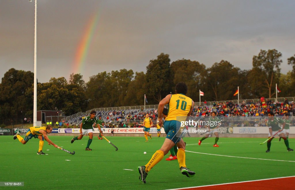 Matthew Swann of Australia passes the ball as a rainbow appears during the match between the Australia and Pakistan during day three of the Champions Trophy at the State Netball Hockey Centre on December 4, 2012 in Melbourne, Australia.