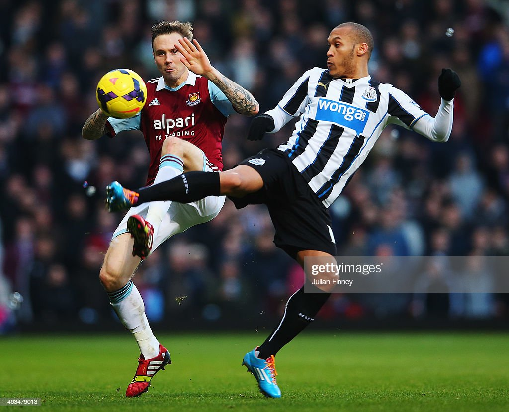 Matthew Taylor of West Ham United and <a gi-track='captionPersonalityLinkClicked' href=/galleries/search?phrase=Yoan+Gouffran&family=editorial&specificpeople=534470 ng-click='$event.stopPropagation()'>Yoan Gouffran</a> of Newcastle United challenge for the ball during the Barclays Premier League match between West Ham United and Newcastle United at the Boleyn Ground on January 18, 2014 in London, England.