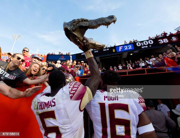Matthew Thomas and Jacob Pugh of the Florida State Seminoles carry a gator head out of Ben Hill Griffin Stadium after the game against the Florida...