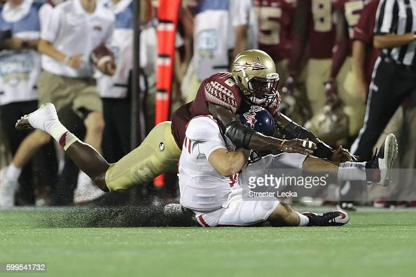 Matthew Thomas of the Florida State Seminoles tackles Chad Kelly of the Mississippi Rebels in the first half during the Camping World Kickoff at...