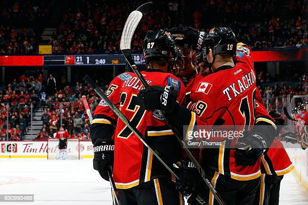 Matthew Tkachuk Michael Frolik and teammates of the Calgary Flames celebrate a goal against the Colorado Avalanche during an NHL game on January 4...