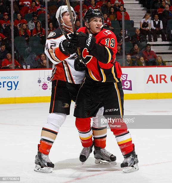 Matthew Tkachuk of the Calgary Flames battles against Josh Manson of the Anaheim Ducks at Scotiabank Saddledome on December 4 2016 in Calgary Alberta...