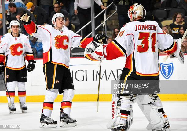 Matthew Tkachuk of the Calgary Flames celebrates with Chad Johnson after defeating the Pittsburgh Penguins in a shootout at PPG Paints Arena on...