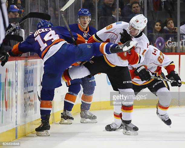 Matthew Tkachuk of the Calgary Flames checks Thomas Hickey of the New York Islanders during the first period at the Barclays Center on November 28...