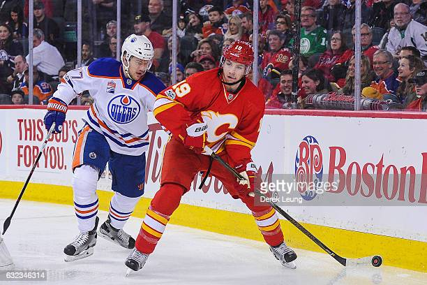Matthew Tkachuk of the Calgary Flames skates with the puck past Oscar Klefbom of the Edmonton Oilers during an NHL game at Scotiabank Saddledome on...