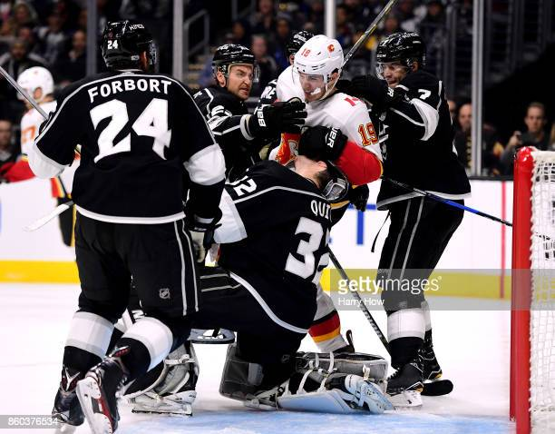 Matthew Tkachuk of the Calgary Flames takes off the mask of Jonathan Quick of the Los Angeles Kings as he is grabed by Trevor Lewis and Oscar...
