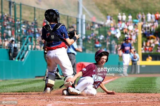 Matthew Vivona of the New England team from Connecticut slides into home against JR Osmond of the MidAtlantic team from New Jersey during Game 2 of...