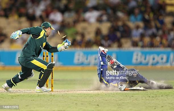 Matthew Wade of Australia breaks the stumps but too late as Chamara Kapugedera of Sri Lanka makes his ground during the third One Day International...