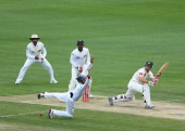 Matthew Wade of Australia gets his shot past Dimuth Karunaratne of Sri Lanka during day two of the First Test match between Australia and Sri Lanka...