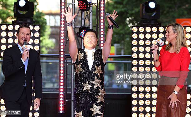 Matthew White and Melissa Doyle look on as South Korean rapper Psy acknowledges the crowd on Channel 7's 'Sunrise' at Martin Place on October 17 2012...