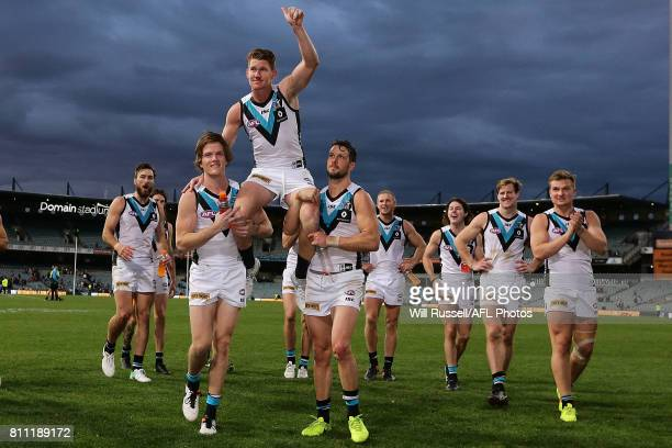Matthew White of the Power is chaired off by Jared Polec and Travis Boak after playing his 150th game during the round 16 AFL match between the West...