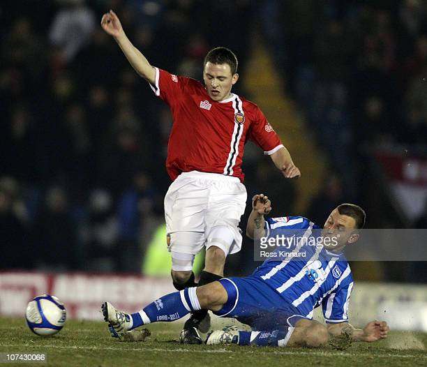 Matthew Wolfenden of FC United is challenged by Gary Hart of Brighton during the FA Cup sponsored by EON 2nd Round Replay between FC United of...