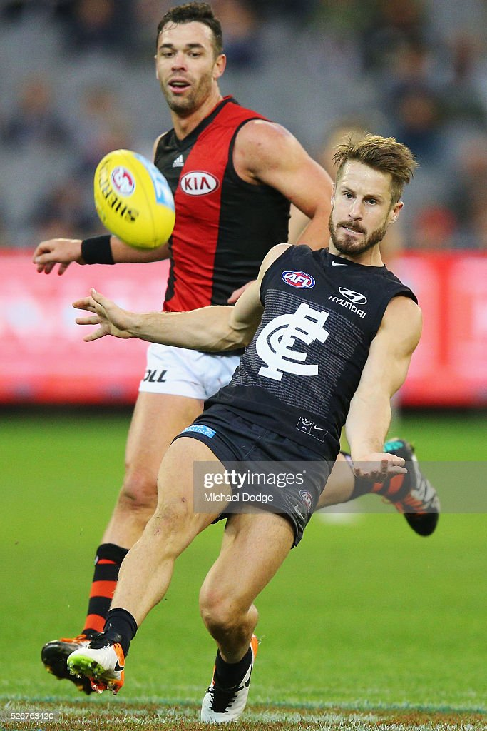 Matthew Wright of the Blues kicks the ball away from Ryan Crowley of the Bombers during the round six AFL match between the Carlton Blues and the Essendon Bombers at Melbourne Cricket Ground on May 1, 2016 in Melbourne, Australia.