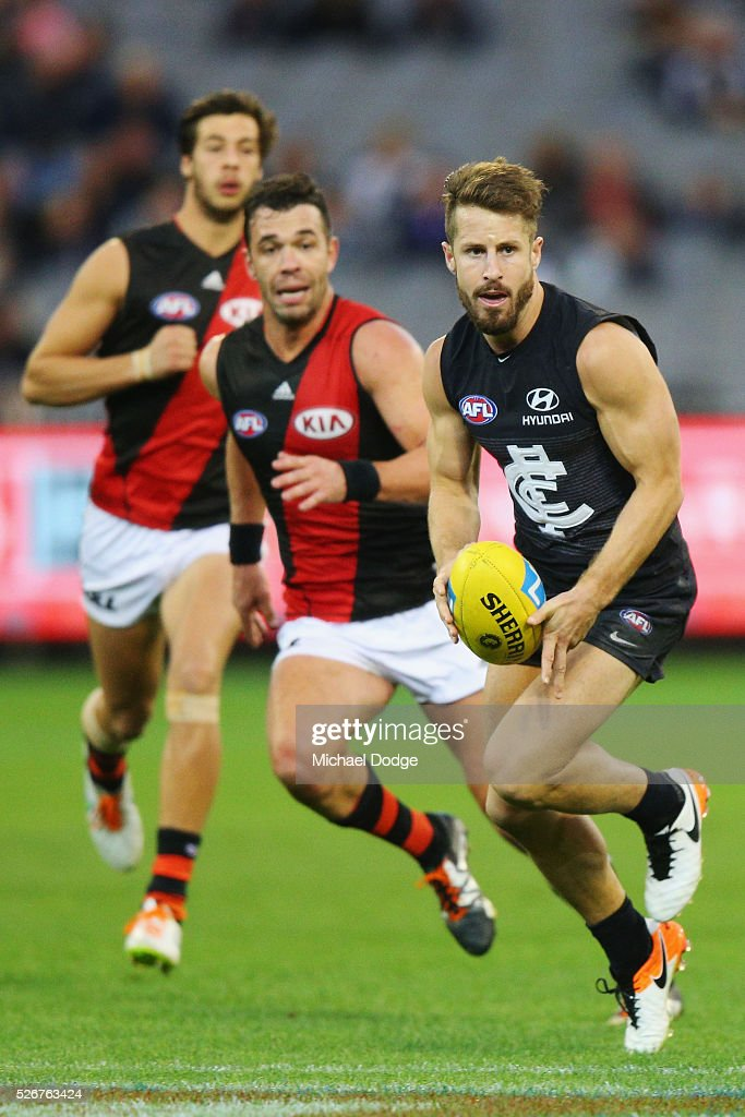 Matthew Wright of the Blues runs with the ball away from Ryan Crowley of the Bombers during the round six AFL match between the Carlton Blues and the Essendon Bombers at Melbourne Cricket Ground on May 1, 2016 in Melbourne, Australia.