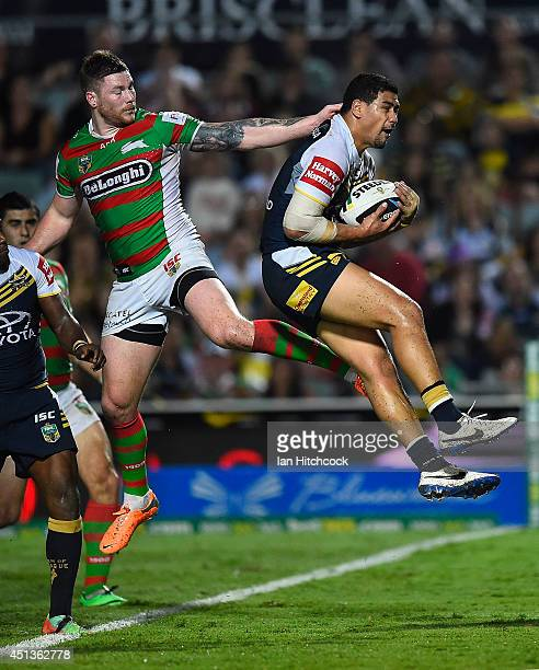 Matthew Wright of the Cowboys takes a high ball in his own in goal with Chris McQueen of the Rabbitohs during the round 16 NRL match between the...