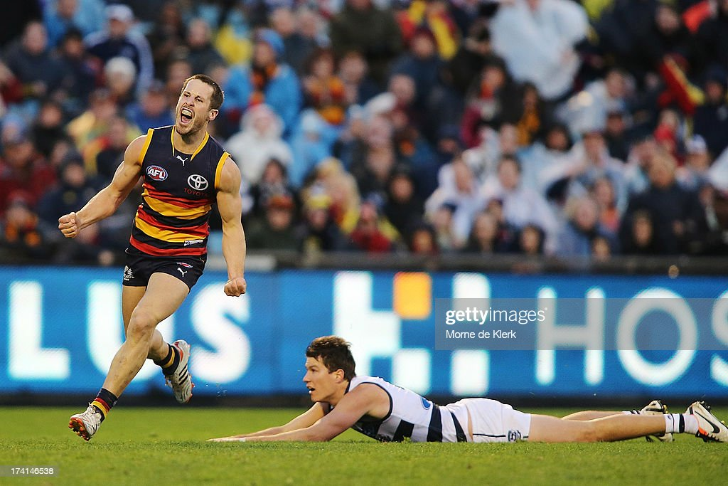 Matthew Wright of the Crows celebrates after kicking a late goal as Andrew Mackie of the Cats looks on during the round 17 AFL match between the Adelaide Crows and the Geelong Cats at AAMI Stadium on July 21, 2013 in Adelaide, Australia.