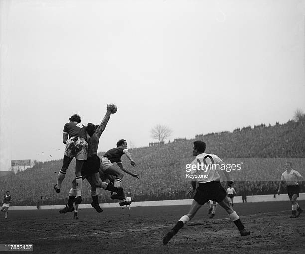 Matthews the Derby goalie punches clear from Dennis Edwards the Charlton Athletic insideleft and Hopkinson the Derby lefthalf during the 4th Round of...
