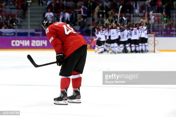 Matthias Bieber of Switzerland skates off the ice as Team Latvia celebrate defeating Switzerland 3 to 1 in the Men's Ice Hockey Qualification Playoff...