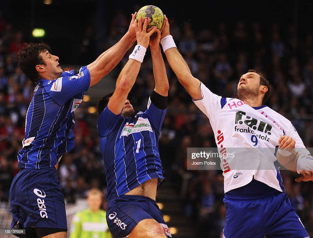 Matthias Flohr (C) of Hamburg is challenged by Jens Tiedtke (R) of Grosswallstadt during the Toyota Handball Bundesliga match between HSV Hamburg and TV Grosswallstadt at the O2 Arena on November 17, 2011 in Hamburg, Germany.
