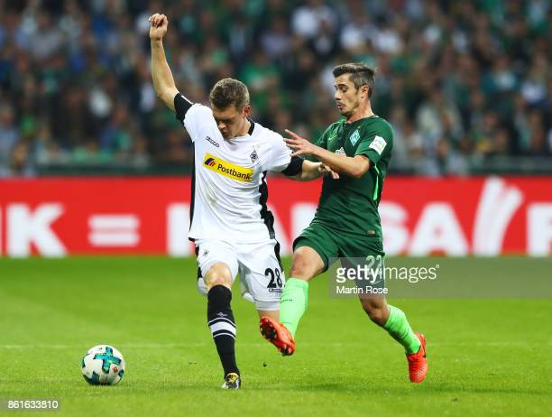 Matthias Ginter of Borussia Moenchengladbach is challenged by Fin Bartels of Werder Bremen during the Bundesliga match between SV Werder Bremen and...