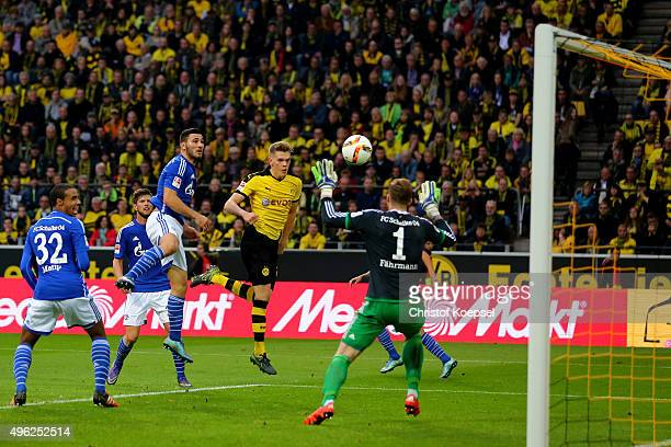 Matthias Ginter of Dortmund scores the second goal against Ralf Faehrmann of Schalke during the Bundesliga match between Borussia Dortmund and FC...