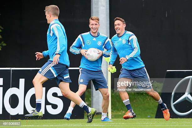 Matthias Ginter of Germany jokes with his team mates Marco Reuss and Max Kruse during a training session of the German national football team at...