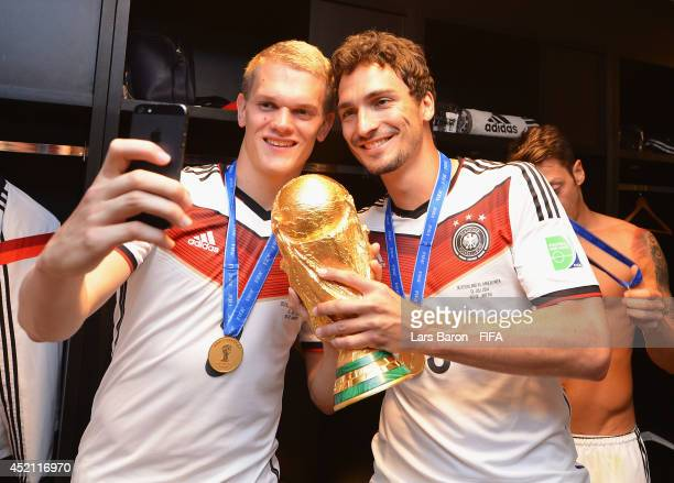Matthias Ginter of Germany takes a photo of himself with Mats Hummels of Germany and the World Cup trophy after the 2014 FIFA World Cup Brazil Final...