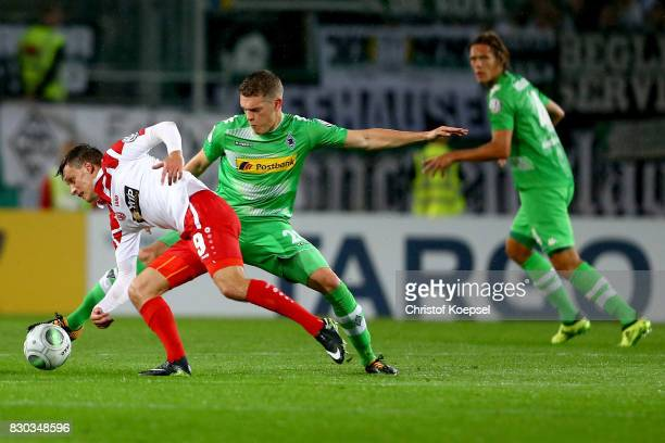 Matthias Ginter of Mnchengladbach challenges Marcel Platzek of Essen during the DFB Cup first round match between RotWeiss Essen and Borussia...