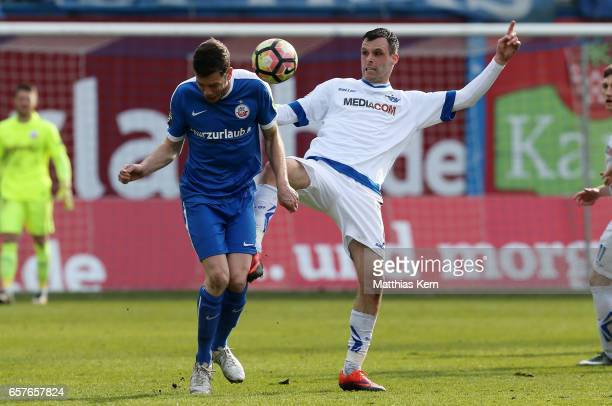 Matthias Henn of Rostock battles for the ball with Koen van der Biezen of Paderborn during the third league match between FC Hansa Rostock and SC...