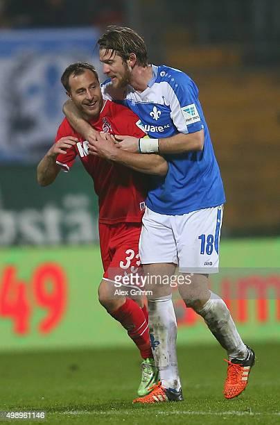 Matthias Lehmann of Koeln is hugged by Peter Niemeyer of Darmstadt during the Bundesliga match between SV Darmstadt 98 and 1 FC Koeln at MerckStadion...