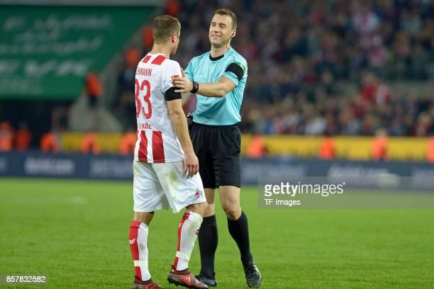 Matthias Lehmann of Koeln speak with referee Felix Zwayer during the Bundesliga match between 1 FC Koeln and RB Leipzig at RheinEnergieStadion on...