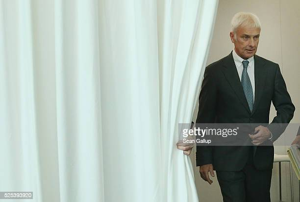 Matthias Mueller CEO of German automaker Volkswagen AG emerges from behind a curtain to speak to television reporters following the company's annual...