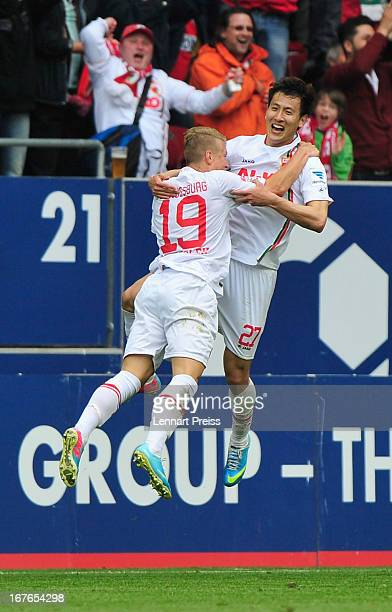 Matthias Ostrzolek and DongWon Ji of Augsburg celebrate a goal during the Bundesliga match between FC Augsburg and VfB Stuttgart at SGL Arena on...