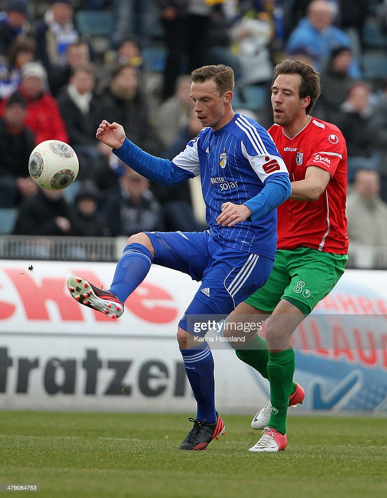 Matthias Pessolat of Jena is challenged by <a gi-track='captionPersonalityLinkClicked' href=/galleries/search?phrase=Rene+Lange&family=editorial&specificpeople=2335154 ng-click='$event.stopPropagation()'>Rene Lange</a> of Magdeburg during the Regionalliga match between FC Carl Zeiss Jena and 1.FC Magdeburg at Ernst Abbe Sportfeld on March 16, 2014 in Jena, Germany.