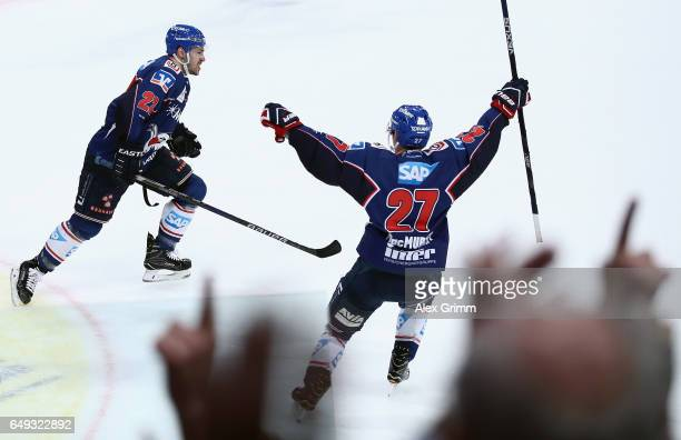 Matthias Plachta of Mannheim celebrates his team's third goal with team mate Ryan MacMurchy during the DEL Playoffs quarter finals Game 1 between...