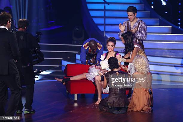 Matthias Steiner and other dancers console Ekaterina Leonova while she rest on a bench after her injury during the final show of the television...