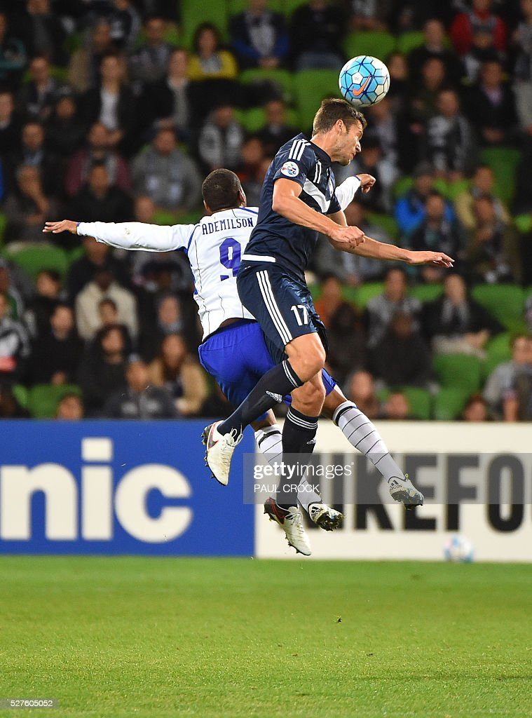 Matthieu Delpierre (R) of Melbourne Victory leaps for the ball against Ademilson of Gamba Osaka during the AFC Champions League football match between the Melbourne Victory and Gamba Osaka in Melbourne on May 3, 2016. / AFP / Paul Crock / IMAGE