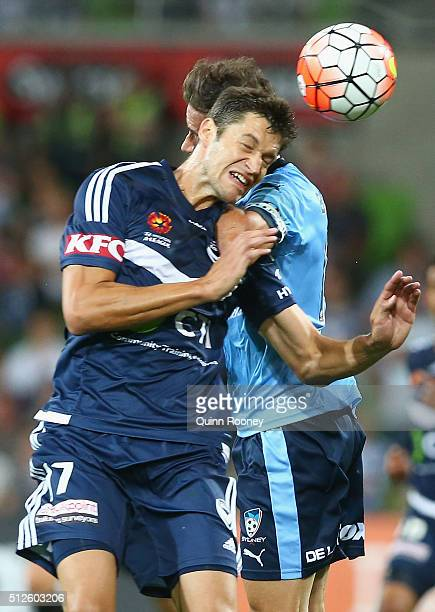 Matthieu Delpierre of the Victory and Alex Brosque of Sydney FC compete to head the ball during the round 21 ALeague match between Melbourne Victory...